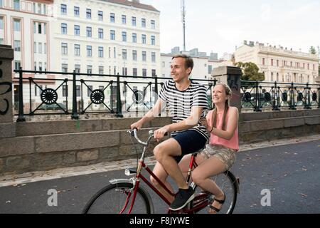 Young man riding bicycle with young woman sitting on back smiling - Stock Photo