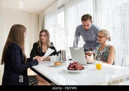 Colleagues at table having breakfast meeting looking at paperwork - Stock Photo