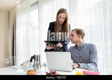 Young woman showing colleague digital tablet at breakfast business meeting - Stock Photo