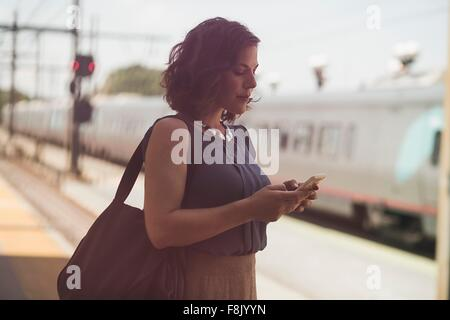 Mid adult woman waiting at train station, holding smartphone - Stock Photo