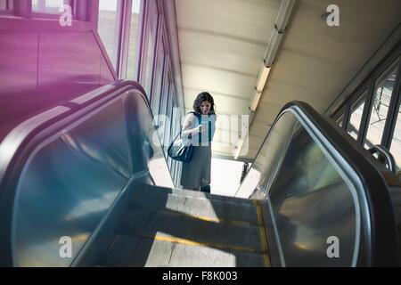Mid adult woman using escalator, holding smartphone, elevated view - Stock Photo