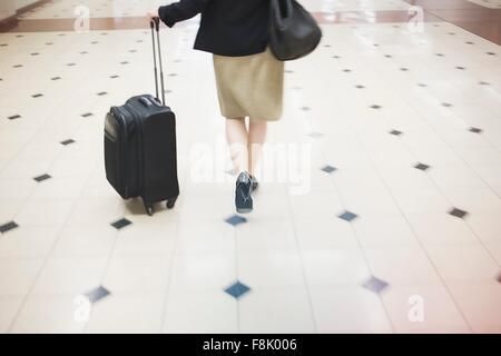 Mid adult woman walking with wheeled suitcase, rear view, low section - Stock Photo