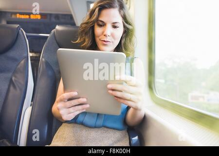 Mid adult woman on train using digital tablet - Stock Photo
