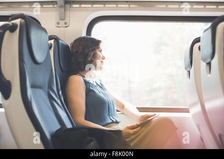 Mid adult woman on train, holding digital tablet, looking out of window - Stock Photo