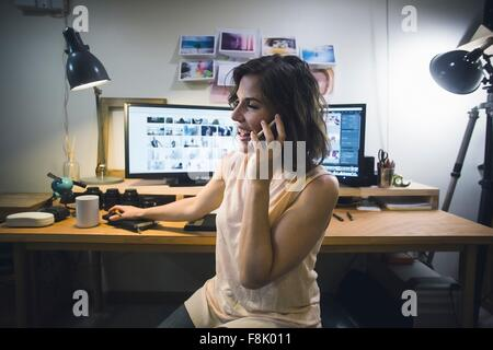 Mid adult woman at desk, using smartphone - Stock Photo
