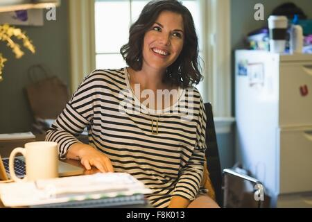 Mid adult woman at desk, laptop and coffee cup in front of her, looking away - Stock Photo