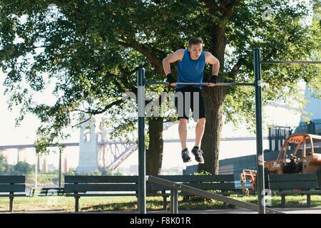 Young man exercising, using bar - Stock Photo
