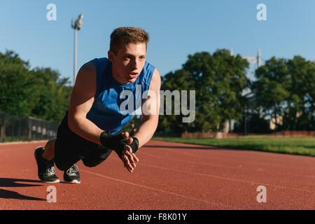 Young man exercising on sports track