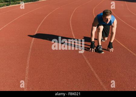 Young man in start position on sports track - Stock Photo