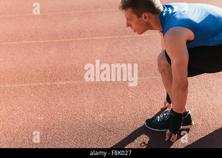 Young man in starting position on sports track - Stock Photo
