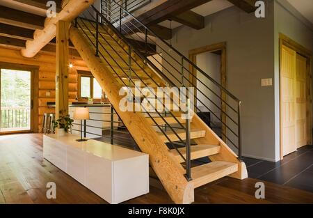 Wood stairway with wrought iron railings in modern Eastern white pine log cabin