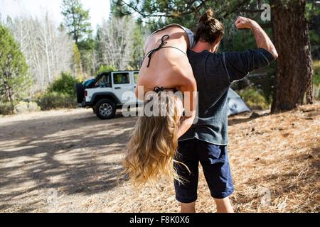 Rear view of young man carrying girlfriend over shoulder at forest campsite, Lake Tahoe, Nevada, USA - Stock Photo