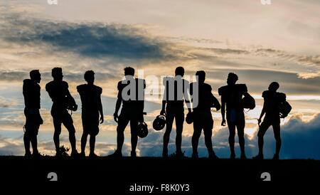 Silhouette of group of young american football players, standing in row - Stock Photo