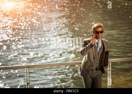 High angle view of young businessman talking on smartphone on city waterfront - Stock Photo