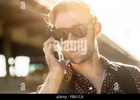 Young businessman wearing sunglasses talking on smartphone on city street - Stock Photo