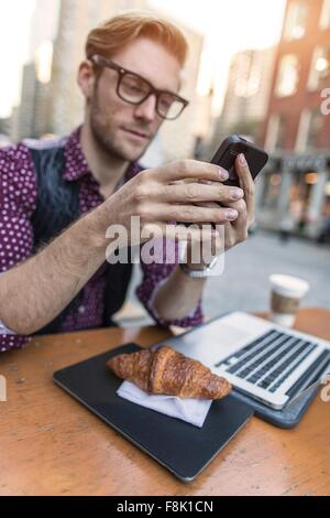 Young businessman having working lunch at sidewalk cafe, New York, USA - Stock Photo