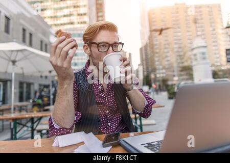 Stressed young businessman hurrying working lunch at sidewalk cafe, New York, USA - Stock Photo