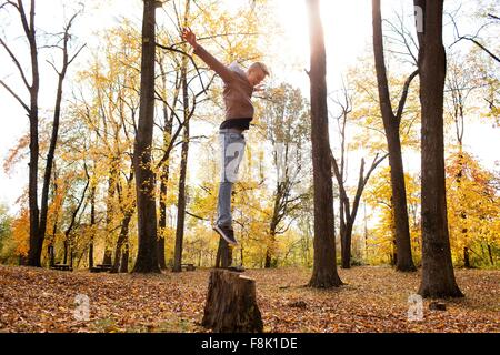 Teenage boy jumping on tree stump in autumn forest - Stock Photo