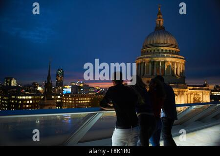 Silhouetted rear view of two young couples looking out to St Pauls at night, London, UK - Stock Photo