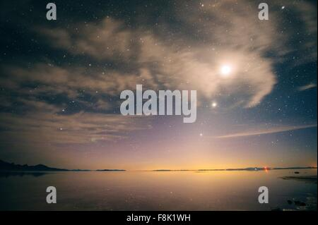 Full moon and starry evening sky over water, Bonneville, Utah, USA - Stock Photo
