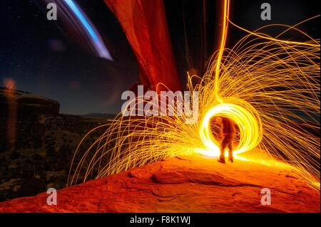 Mature man creating long exposure light painting on cliff side, Moab, Utah, USA - Stock Photo