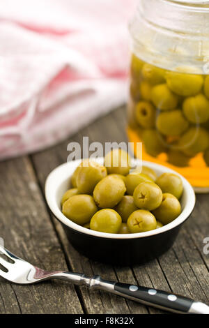 pitted green olives in bowl on wooden table - Stock Photo