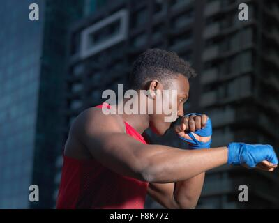 Portrait of boxer throwing punch, building in background - Stock Photo