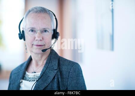 Front view of mature woman wearing telephone headset looking at camera - Stock Photo