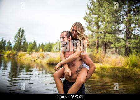 Young man giving girlfriend piggyback in river, Lake Tahoe, Nevada, USA - Stock Photo