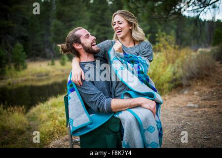 Romantic young couple wrapped in blanket on riverside, Lake Tahoe, Nevada, USA - Stock Photo