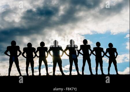 Silhouette of group of young american football players, standing in row, hands on hips - Stock Photo