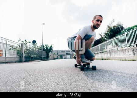 Young man crouched on skateboard - Stock Photo