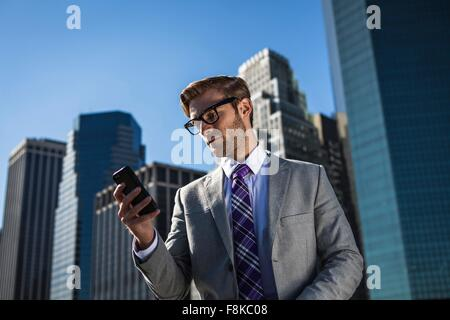 Young businessman in front of office building reading smartphone texts, New York, USA - Stock Photo