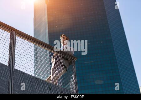Low angle view of young businessman chatting on smartphone on city balcony, New York, USA - Stock Photo