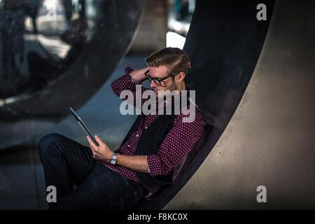 Young businessman reclining on curved wall reading digital tablet - Stock Photo