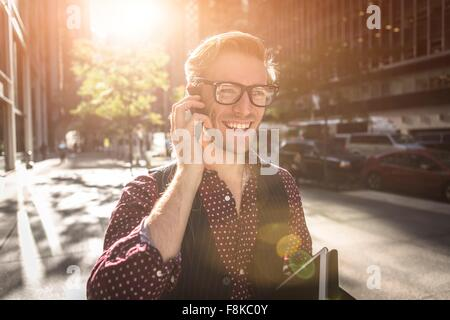 Happy young businessman strolling city street talking on smartphone, New York, USA - Stock Photo