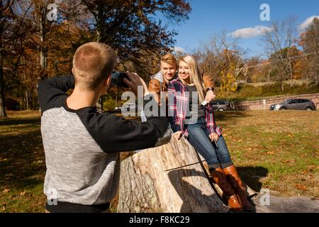 Teenage boy photographing brother and adult sister in autumn park - Stock Photo