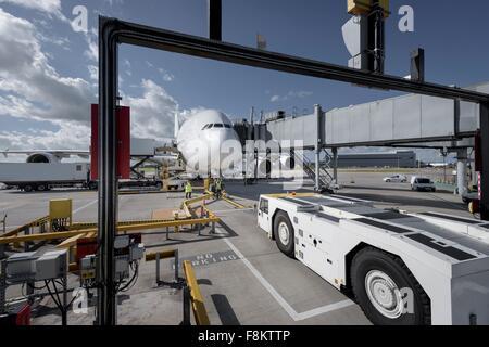 A380 aircraft and tug at stand at airport - Stock Photo