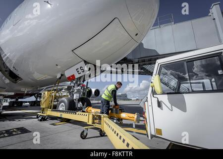 Ground crew attaching tow bar to A380 aircraft - Stock Photo