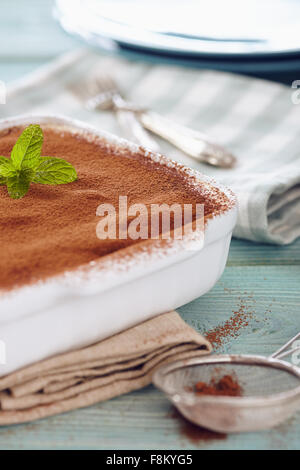 Tiramisu cake in an oven pan on a blue wooden  table with dishes and forks - Stock Photo