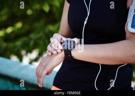Cropped shot of young female runner setting smartwatch - Stock Photo