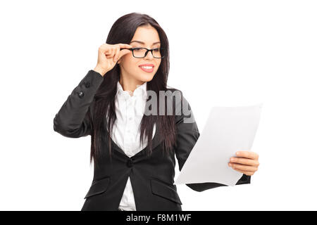 Studio shot of a young businesswoman looking at a document isolated on white background - Stock Photo