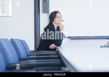 Telephonist contemplating in meeting room - Stock Photo