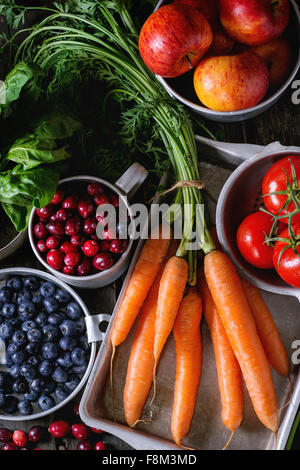 Assortment of fresh fruits, vegetables and berries. Bunch of carrots, spinach, tomatoes and red apples, blueberries - Stock Photo