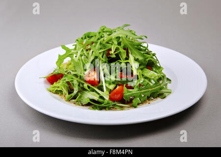 The close up shot of ruccola and cherry tomatoes salad - Stock Photo