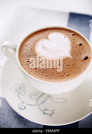 Cup of hot chocolate with whipped cream shaped heart - Stock Photo