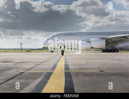 Chief engineer walking from runway as A380 aircraft departs from airport - Stock Photo