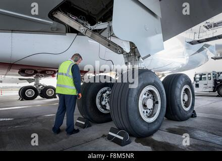 Engineer inspecting A380 aircraft at stand in airport - Stock Photo