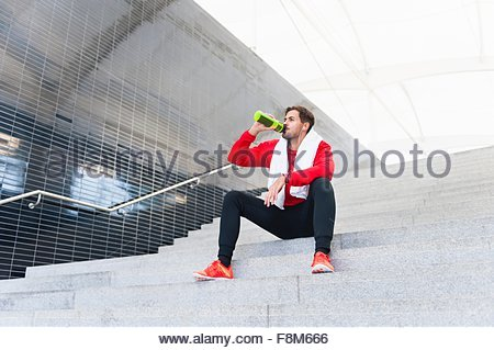Young male runner drinking water bottle on city stairway - Stock Photo