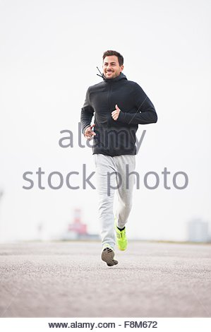 Happy young male runner running in sport arena - Stock Photo